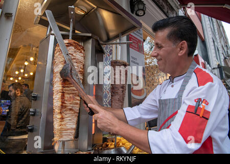 Chef cutting chicken kebab from a street food stall in Istanbul in Turkey. - Stock Image
