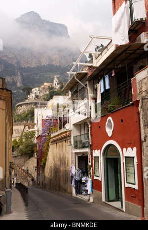 A backstreet in Positano with steep hills in the background. Amalfi Coast, Campania, Italy - Stock Image