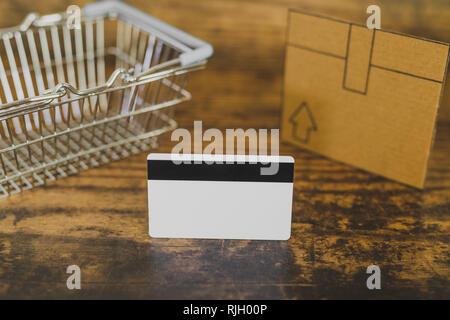empty shopping basket with payment card and delivery box, concept of purchases and expenses - Stock Image