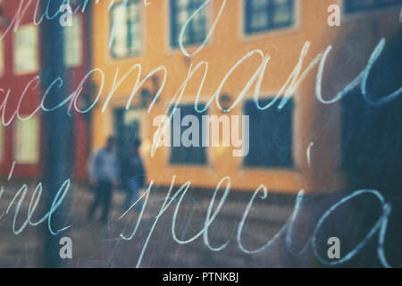 City in reflection of a storefront with text - Stock Image