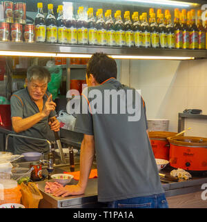 In a restaurant a man giving another man instructions and pointing his finger. - Stock Image