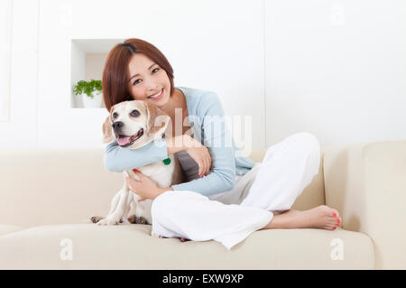 Young woman sitting on the sofa with her dog and smiling at the camera, - Stock Image
