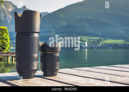 Digital camera lenses standing on wooden board with mountain landscape at background. Copy space background - Stock Image