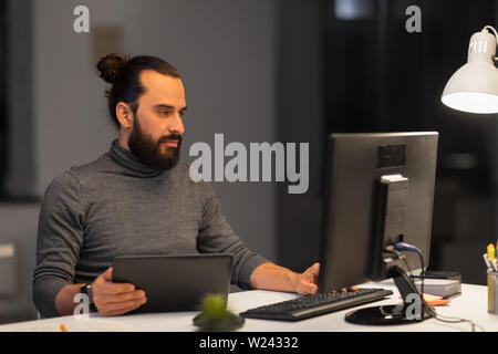 creative man with computer working at night office - Stock Image