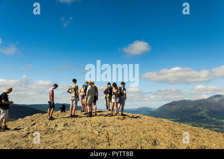 Walkers enjoy the experience of reaching the summit of  Cat Bells (451 metres) near Keswick, Cumbria. Cat Bells is one of the more easily accessible L - Stock Image