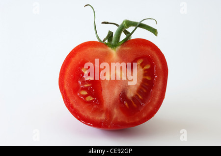 Tomato (Lycopersicon esculentum), halved fruit. Studio picture against a white background. - Stock Image
