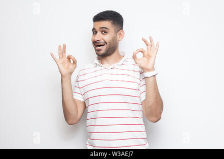 Portrait of funny handsome bearded young man in striped t-shirt standing with Ok sign and looking at camera with happiness. indoor studio shot, isolat - Stock Image