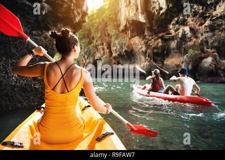Beautiful lady and friends walks by kayaks at sea bay between big rocks - Stock Image