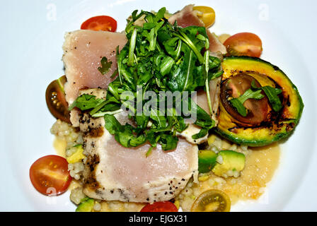 Seared albacore tuna arugula grilled avocado heritage cherry tomato halves over couscous - Stock Image