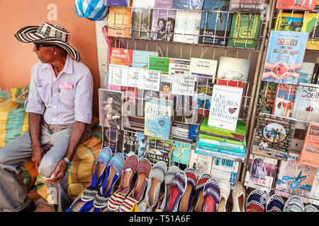 Cartagena Colombia Old Walled City Center centre Centro Hispanic resident residents man sidewalk street book vendor seller artisanal textile shoes dis - Stock Image