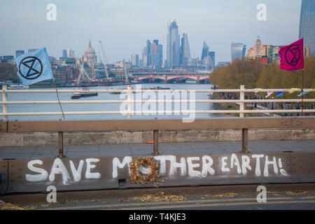 A 'Save Mother Earth' banner painted on Waterloo Bridge for the Extinction Rebellion demonstration with hte City of london behind - Stock Image