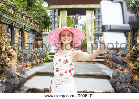 Young woman taking selfie at temple - Stock Image