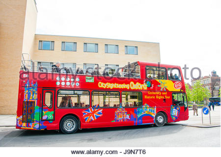 The red tourist City sightseeing Bus leaving Oxford main railway station in Oxfordshire, England UK. The bus travels - Stock Image