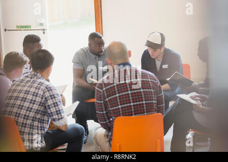 Men reading and discussing bible in circle in prayer group - Stock Image