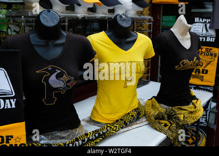 Women's shirts adorned with images of Pittsburgh, Pennsylvania's sports teams on display on mannequins on the sidewalk outside of a Pittsburgh store. - Stock Image