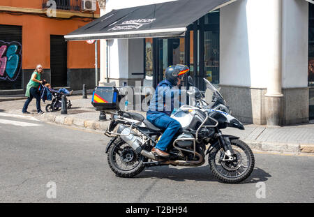 Woman pushing a baby carriage and a man on a motorbike - Stock Image