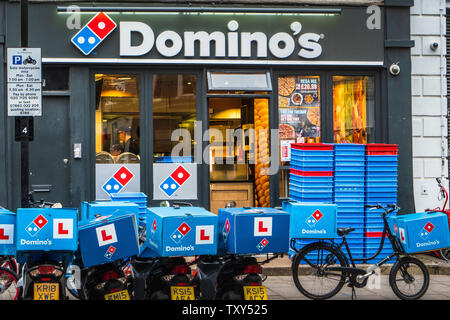 Domino's Pizza Delivery bikes outside a Domino's Pizza takeaway restaurant in Central London UK - Stock Image