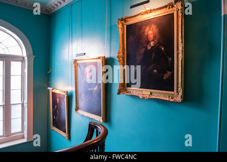 18th and 19th century portraits hanging on the wall of a staircase inside a stately home - Stock Image