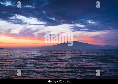 Amazing colorful sunset with dramatic sky over the sea with mountain island at the distance - Stock Image