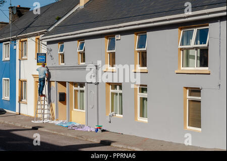 Man on a step ladder painting a house in Drimoleague, West Cork, Ireland on a sunny day - Stock Image