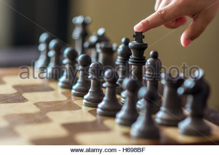 Normal wooden chess board with metal chess pieces. A finger points to a piece to move, in this case the one of the - Stock Image