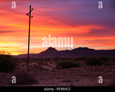 Sunset sky of orange and yellow in the vast  Karoo of South Africa. With silhouette of telephone pole and wires leading to mountain range - Stock Image