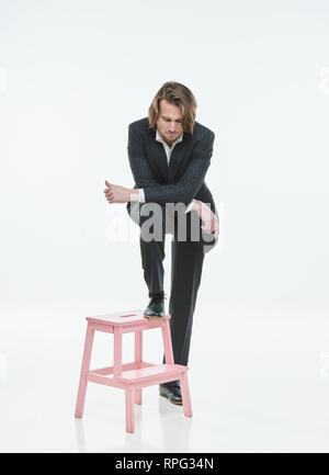 The handsome men in black suits differently pose on a white background, brutal man with long curly hairs, white shirts, business man, very stylish, pink chair - Stock Image