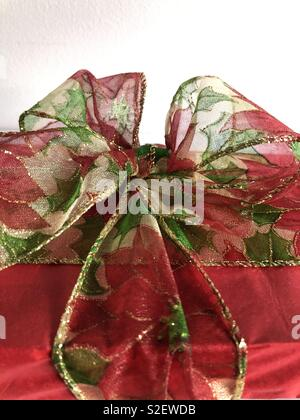 Christmas present decorated with a fabric poinsettia ribbon tied in a flamboyant bow - Stock Image