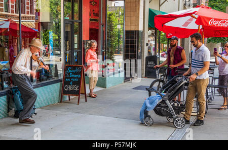 ASHEVILLE, NC, USA-24 JUNE 18: A senior street musician playing a fiddle, dancing and singing, while being watched by several people. - Stock Image