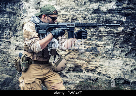 Private military contractor in baseball cap with assault rifle in the rocks. - Stock Image