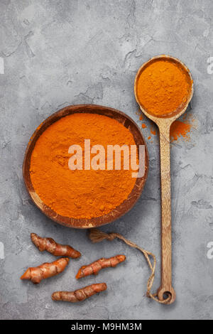 turmeric powder in a coconut bowl, turmeric roots on a gray concrete background. view from above - Stock Image
