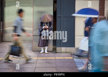 A Shintoist monk asking for alms in the street in Fukuoka, Japan, surrounded by motion blurred pedestrians. - Stock Image