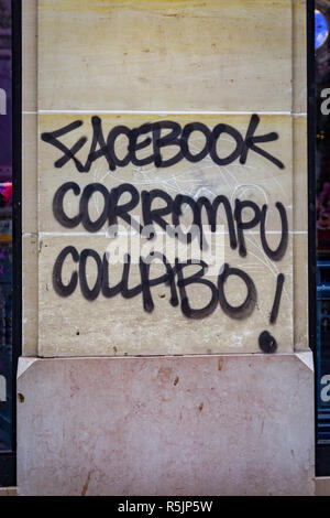Paris, France. 1st December, 2018.  'Facebook corrupt' painting a wall  during the Yellow Vests protest against Macron politic. Credit: Guillaume Louyot/Alamy Live News - Stock Image