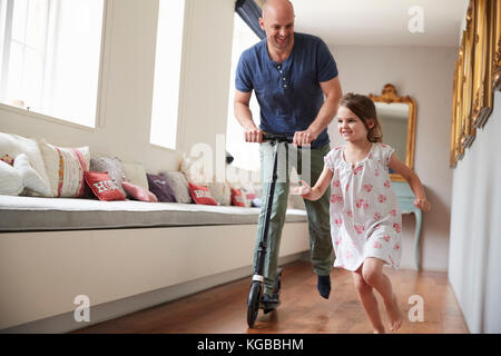 Dad on scooter following as  daughter runs through the house - Stock Image