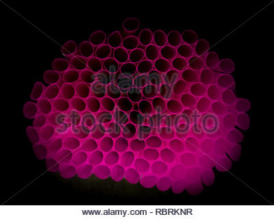 pink purple color straw, plastic product, dark background - Stock Image