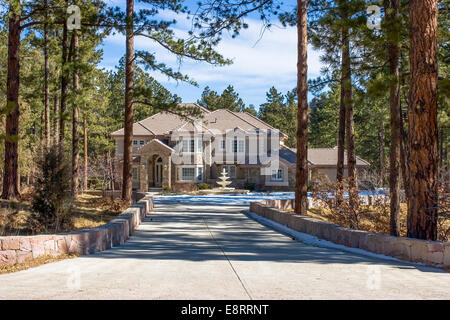 A mansion amongst pine trees in winter with a fountain and snow in the driveway in Perry Park, Colorado - Stock Image