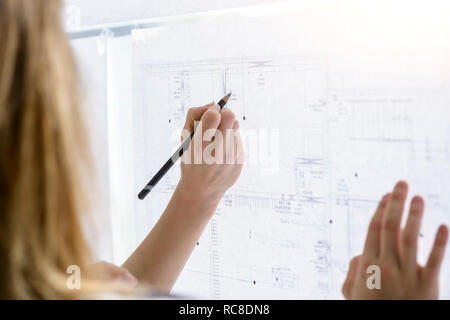 Colleagues discussing plans on glass wall - Stock Image