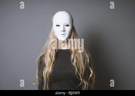 mysterious woman hiding face and identity behind plain white mask - lack of emotion concept - Stock Image