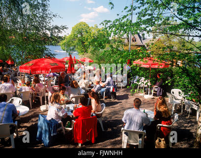 Families and visitors at Cafe Amadeus sharing summer food and conversation  in scenic Djurgarden Djurgården - Stock Image