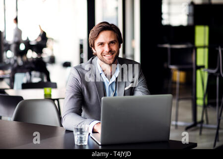 A portrait of happy young businessman with computer in an office, looking at camera. - Stock Image