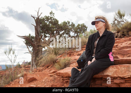 woman hiker resting on Cathedral Rock Trail in Sedona Arizona - Stock Image