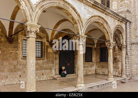 Girl Sitting At Entrance To Sponza Palace Dubrovnik Croatia - Stock Image