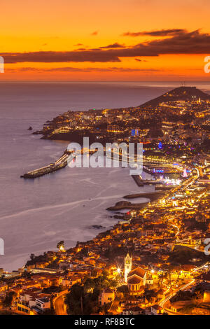 Funchal madeira Funchal skyline at sunset looking across the bay port harbour and old town Funchal Madeira Portugal Europe - Stock Image