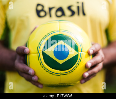 Man holding football with Brazilian flag for Brazil World Cup 2014. - Stock Image