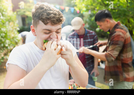 Hungry teenage boy eating hamburger at backyard barbecue - Stock Image