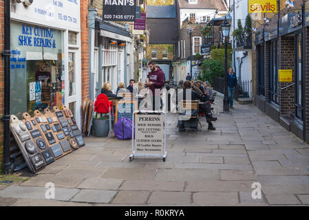 People socialising and enjoying refreshments in restaurant outdoor dining area, Perrin's Court, Hampstead, London, England, UK. - Stock Image