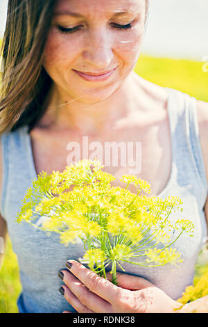 Smiling woman with yellow flower - Stock Image