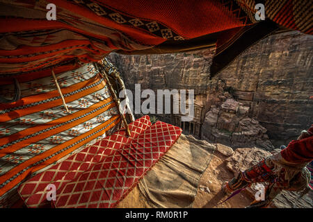 The colourful blankets and comfortable cushions of a cliffside Bedouin tent frame the facade of the famed Treasury of Al Khazneh. - Stock Image
