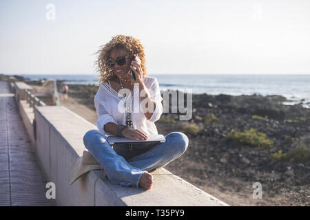 Young beautiful caucasian woman call at the phone speaking at the beach - laptop on his legs for modern trtaveler technology concept - summer vacation - Stock Image