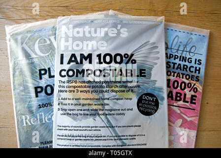 Selection of magazine in compostable covers or packaging including RSPB's Nature's Home, Kew magazine and Ocado Life on kitchen table. - Stock Image
